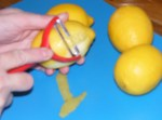 Using a vegetable peeler to remove the rind from a lemon